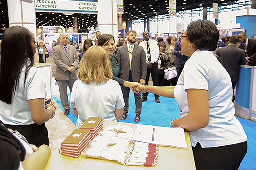 photo of secretary pritzker meeting other at the supplier diversity booth